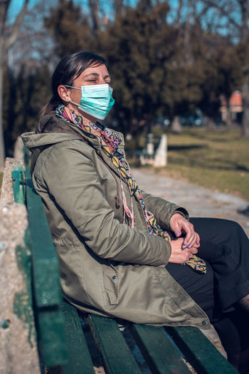 Side view of young woman sitting on bench in winter