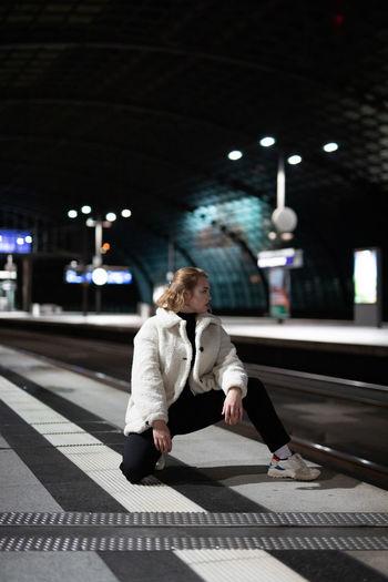 Woman standing on railroad station platform at night