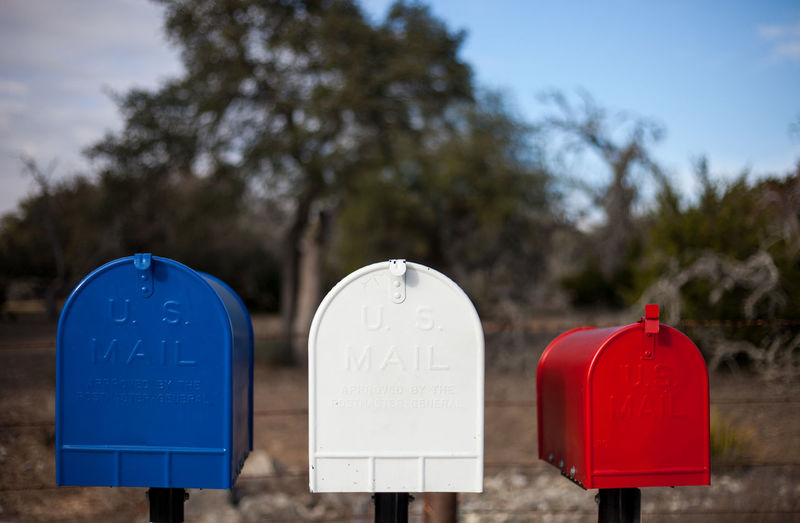 Close-up of mailboxes against trees