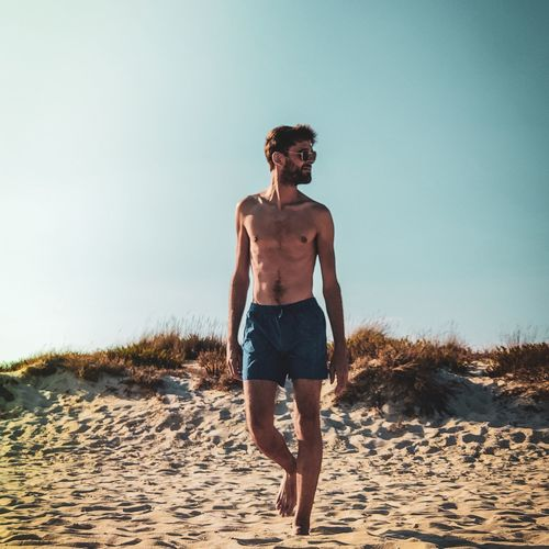Full length of shirtless man walking at beach against clear sky