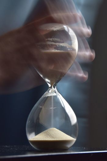 Blurred motion of hand holding hourglass