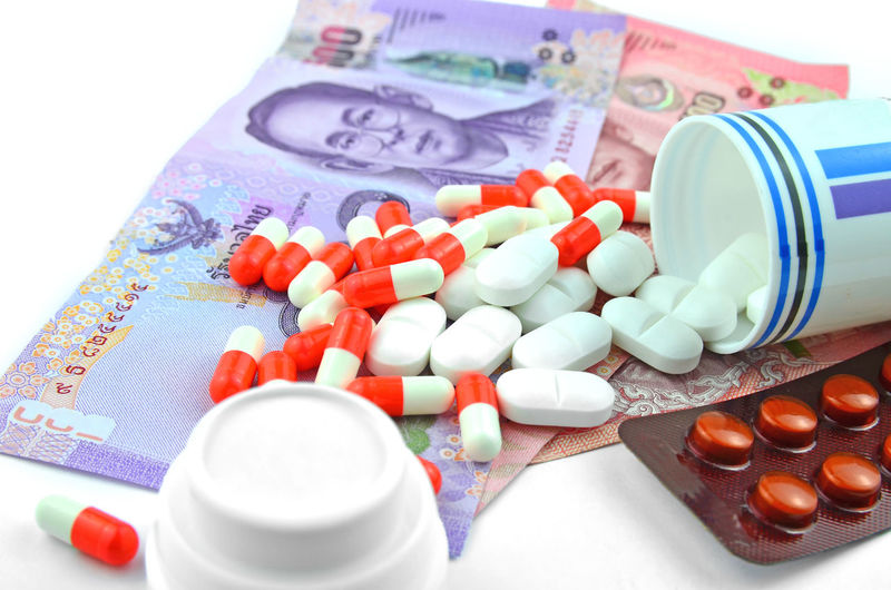 Close-up of medicines and paper currency over white background