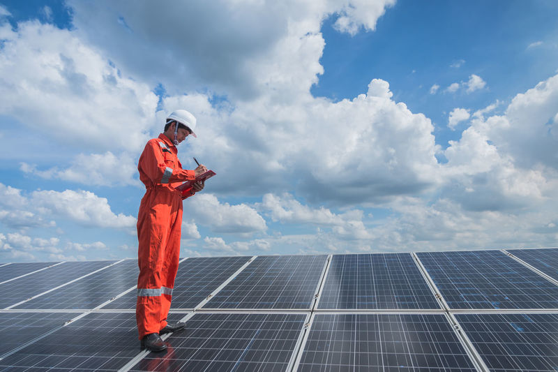 Engineer standing on solar panel against cloudy sky