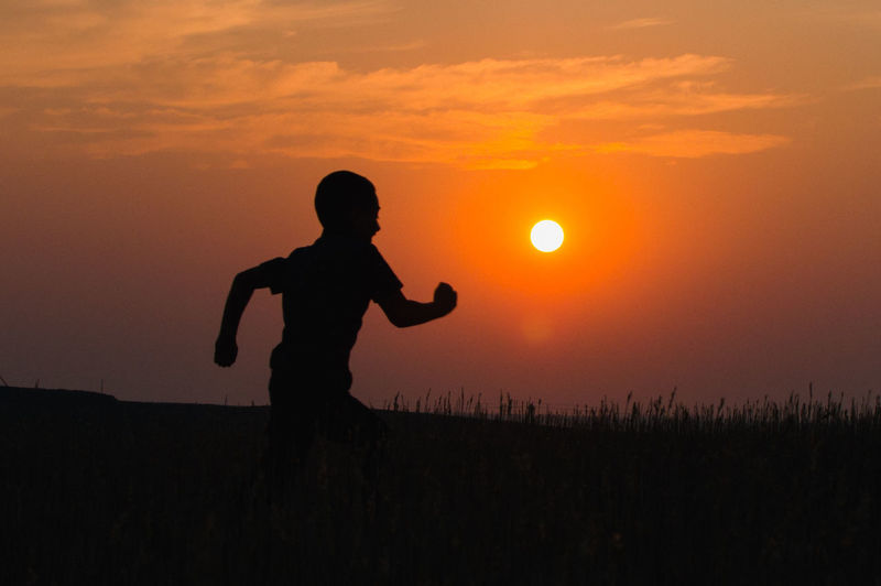 Silhouette boy standing on field against sky during sunset