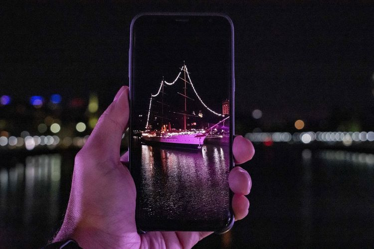 Person holding mobile phone in river at night