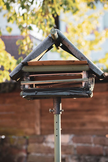 Low angle view of birdhouse on roof against wall