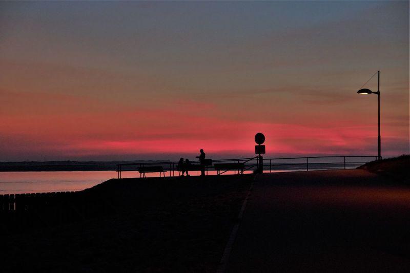 Silhouette people on street by sea against orange sky