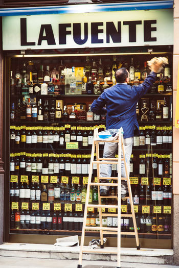 Boutique Cleaning Lifestyle Alcohol Bottle Casual Clothing Clean Freshness Full Length Lifestyle Photography Lifestyles Men Occupation One Man Only One Person People Real People Rear View Retail  Shelf Standing Store Streetphotography Supermarket Working