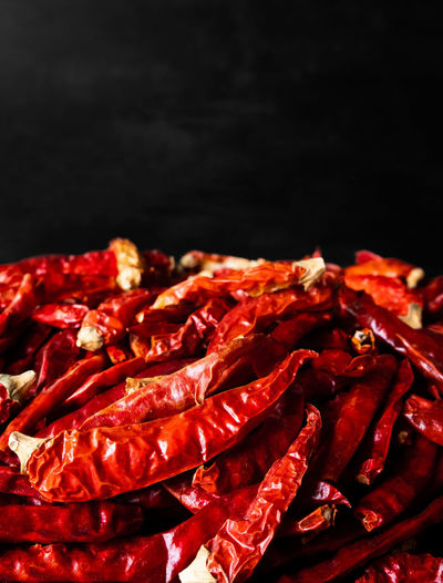 Close-up of red chili peppers against black background
