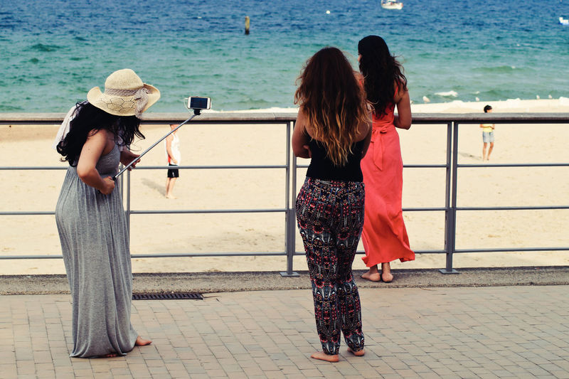 Rear view of women standing by railing against sea