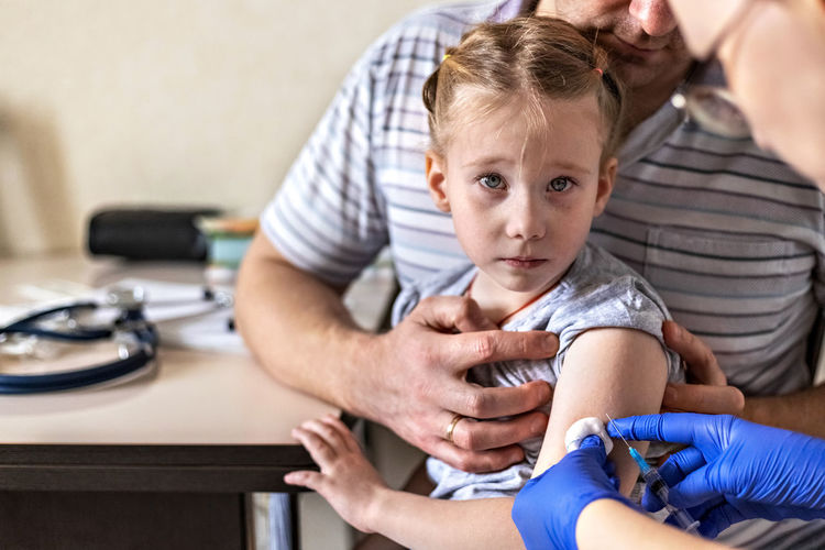 A little girl  in the doctor's office . the concept of vaccination prevention against covid-19