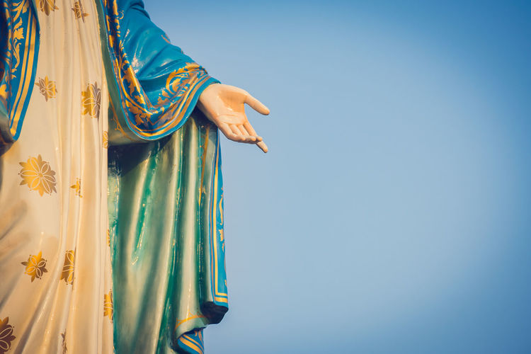 Low angle view of virgin mary statue against clear blue sky
