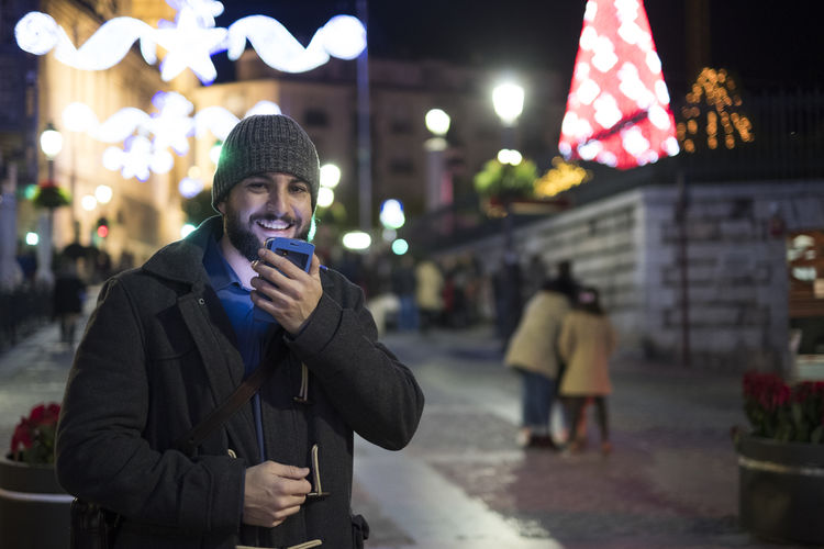 night scene of man using smartphone in night Christmas City Light Man Social Networking Beard Bokeh Communication Focus On Foreground Hipster Illuminated Lifestyles Men Message Mobile Phone Night One Person Outdoors Phone Real People Smartphone Standing Technology Voice Wireless Technology Young Adult