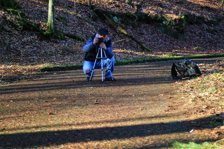 Man photographing on footpath