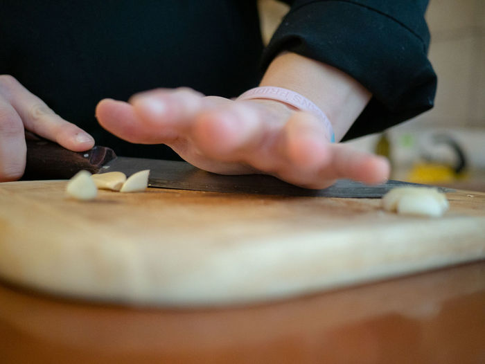 Midsection of person preparing food on cutting board at home