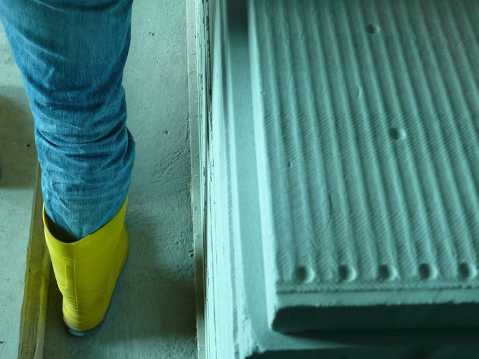 Low section of worker wearing rubber boot at construction site
