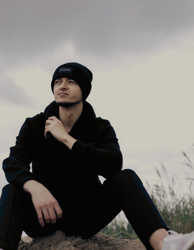 Young man looking away while sitting against sky