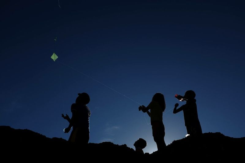 Low angle view of children flying kites against clear sky