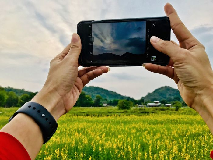 Human Hand Hand Technology Sky Human Body Part Photography Themes Nature Plant Photographing Holding Field One Person Smart Phone Wireless Technology Cloud - Sky