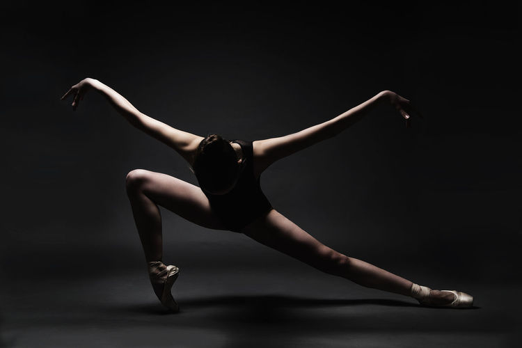 Adult Adults Only Balance Ballet Ballet Dancer Beauty Black Background Dancer Dancing Elégance Expertise Flexibility Full Length Grace Legs Apart Modern Motion One Person People Performance Performing Arts Event Skill  Stretching Studio Shot Young Adult