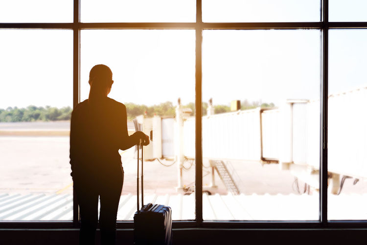 Rear view of silhouette woman standing at airport terminal