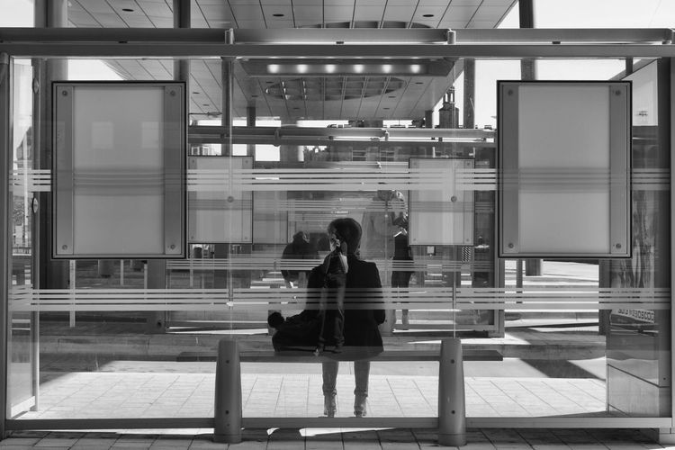 Rear view of woman sitting on bus stop