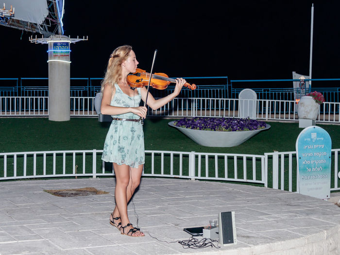 Nahariya, Israel, July 26, 2017 : The young girl in the summer evening plays for passers-by on the violin on the waterfront of Nahariya, Israel Artistic Beautiful Hair Music Nahariya Young Art Attractive Classical Entertainment Girl Instrument Israel Melody Musical Musician Night One Person Performance Play Player Pretty Standing Violin Waterfront