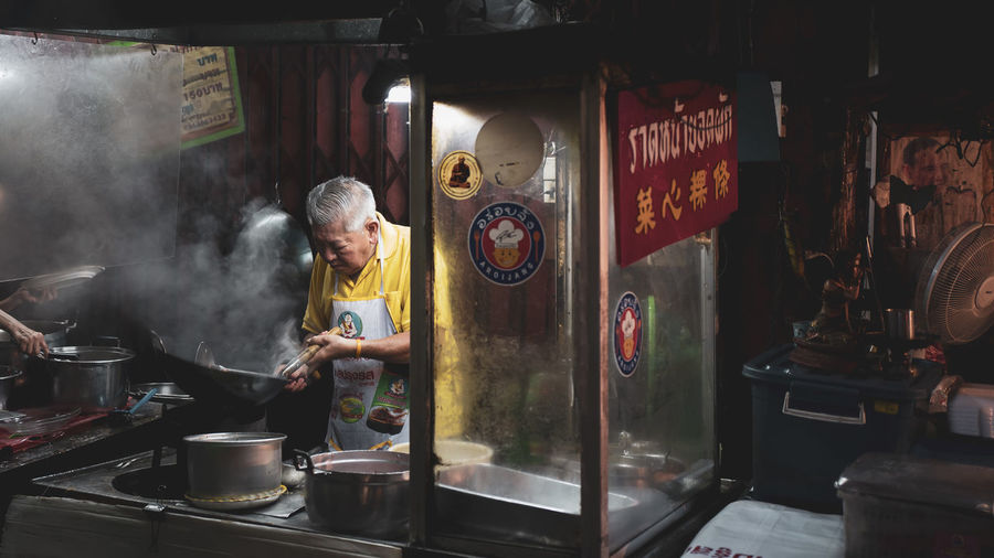 Real People One Person Men Indoors  Preparation  Occupation Business Standing Small Business Smoke - Physical Structure Holding Food And Drink Preparing Food Working Adult Males  Senior Adult Food Market Chef