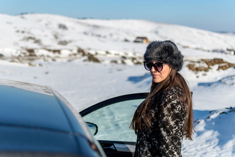 Portrait of woman standing by car on snow covered land