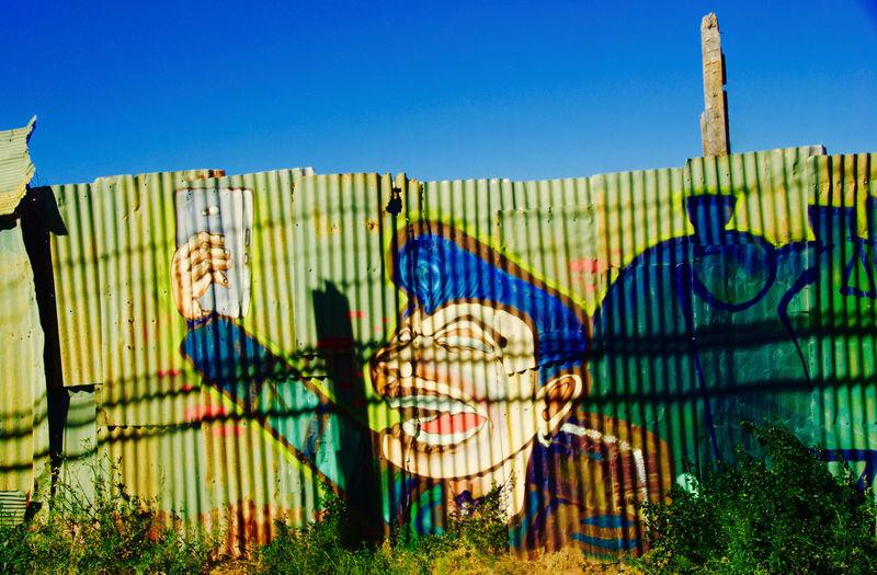 Graffiti on beach against clear blue sky