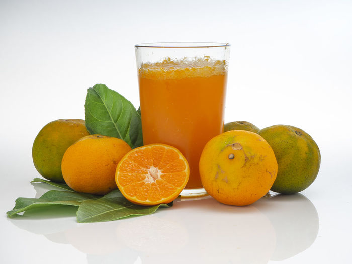 Food And Drink Healthy Eating Fruit Freshness Drinking Glass Food Drink Refreshment Wellbeing Household Equipment Glass Citrus Fruit Leaf White Background Orange Color Studio Shot Orange - Fruit Indoors  Orange Plant Part No People Mint Leaf - Culinary Non-alcoholic Beverage Fruit Juice
