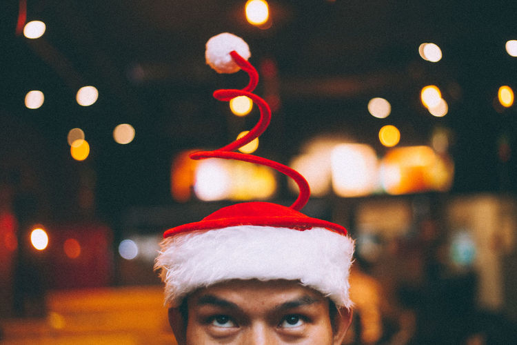 A man with an usual Christmas Hat Taken on the day before Christmas Eve Christmas Creativity Event Holiday Love Man Celebration Christmas Christmas Decoration Christmas Lights Christmas Tree Close-up Eyes Focus On Foreground Holiday - Event Illuminated Indoors  Night One Person People Portrait Real People Santa Hat Spring Young Adult