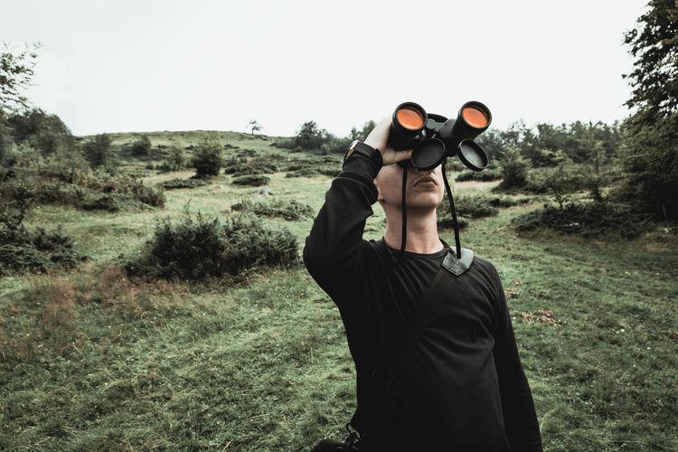 Hiker looking through binoculars in front of hills and mountain range. Prevalla, Prizren, Kosovo Binoculars Hill Hiker Environment Field Nature Landscape Leisure Activity Looking Up Lifestyle Outdoors Birdwatching Observation Outdoor Grass Field High Male Standing Trekking 17.62°
