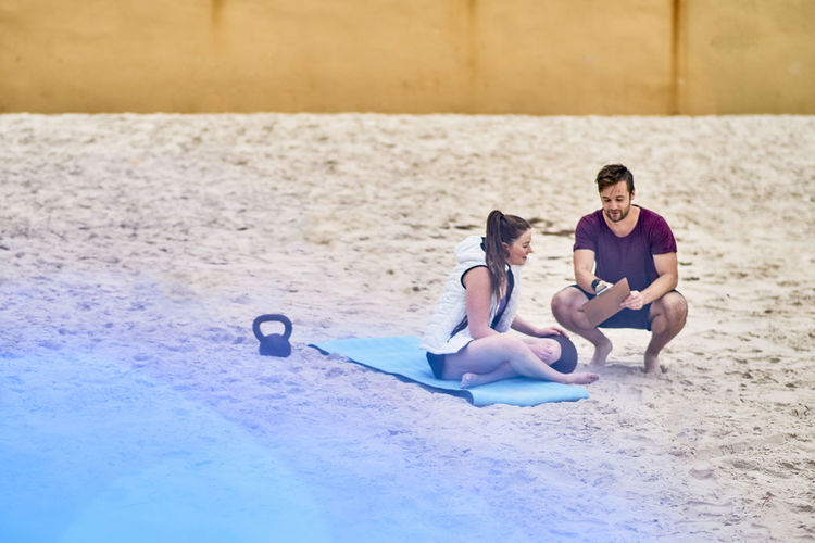 Fitness Instructor Assisting Woman In Exercising At Beach