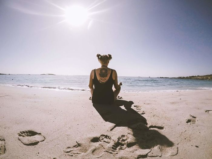 Rear View Of Woman Sitting At Beach Against Sky During Sunny Day