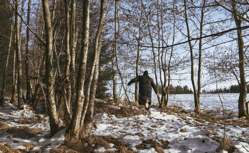 Rear view of man on snow covered land