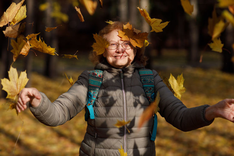 Portrait of smiling woman standing with leaves during autumn