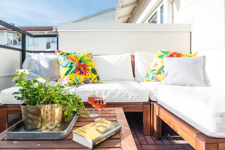 Book and drink by potted plants on side table by sofa in patio