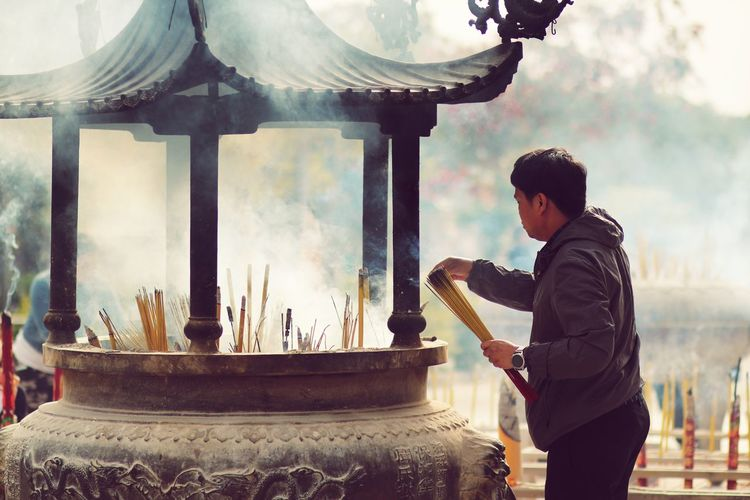 Man holding incense while standing against temple