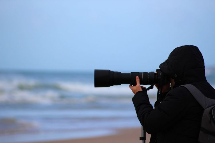Side view of photographer with dslr at beach against sky