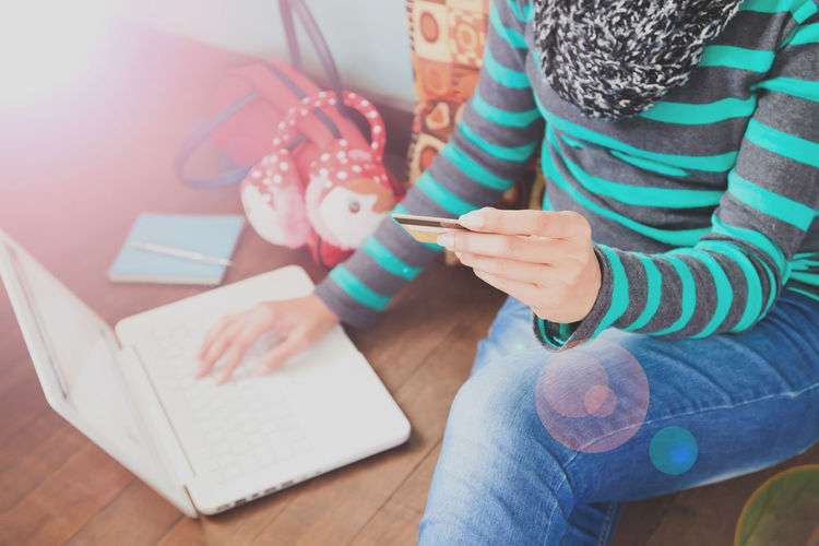Close-up of woman using laptop while sitting on floor
