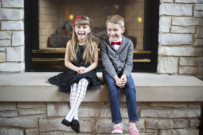 Christmas Siblings Child Fireplace Happiness Looking At Camera Portrait Sitting Smiling