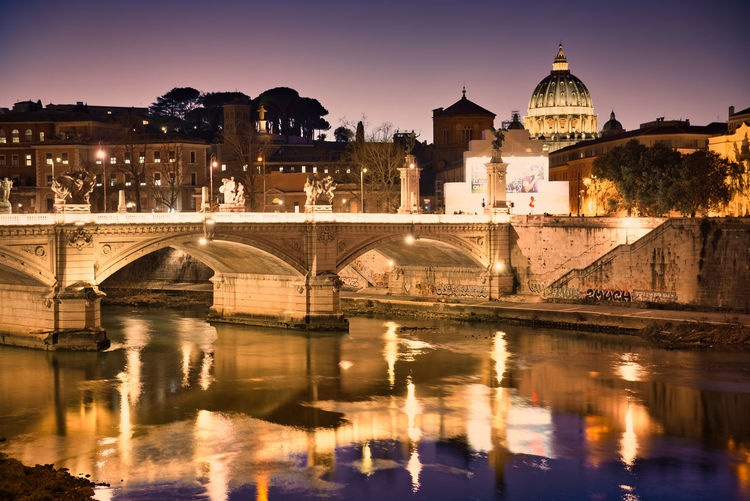 View of st. peter's basilica from tiber river in rome at twilight