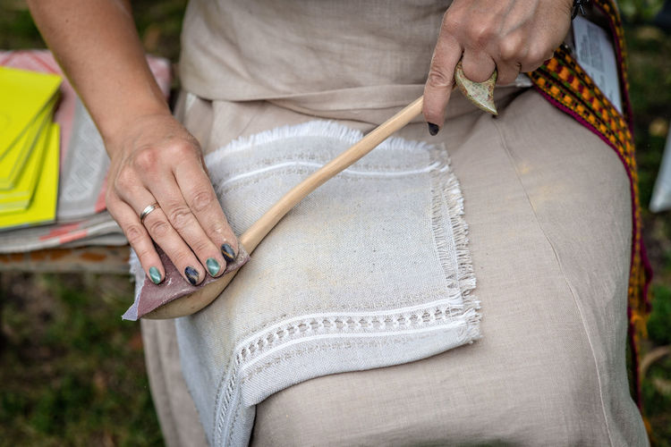 Midsection of woman cleaning wooden spoon