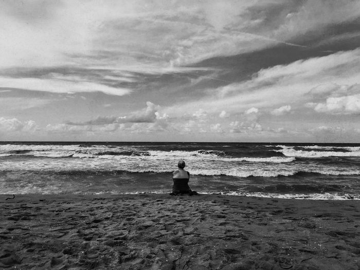 Rear View Of Woman Sitting On Shore At Beach Against Sky