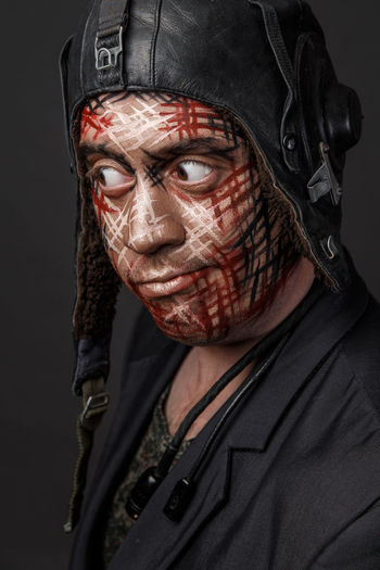 Close-up of man with face paint against black background