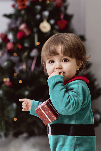 Portrait of cute girl holding christmas tree