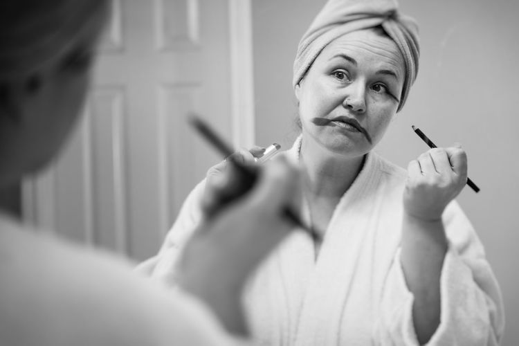 Mature woman applying make-up reflecting on mirror at home
