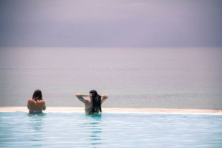 Rear View Of Women In Infinity Pool Against Sea