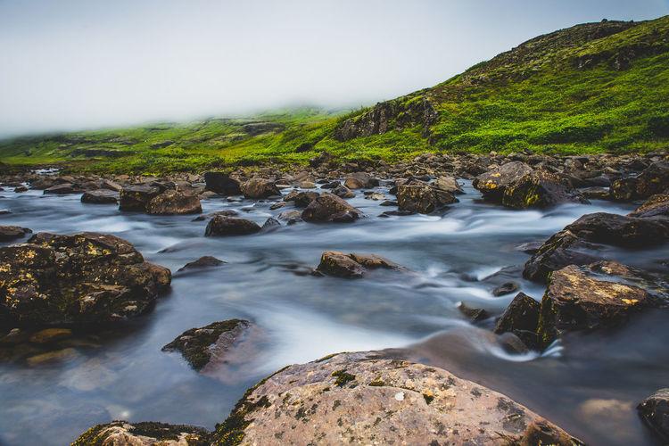 Stream flowing through rocks in sea against sky
